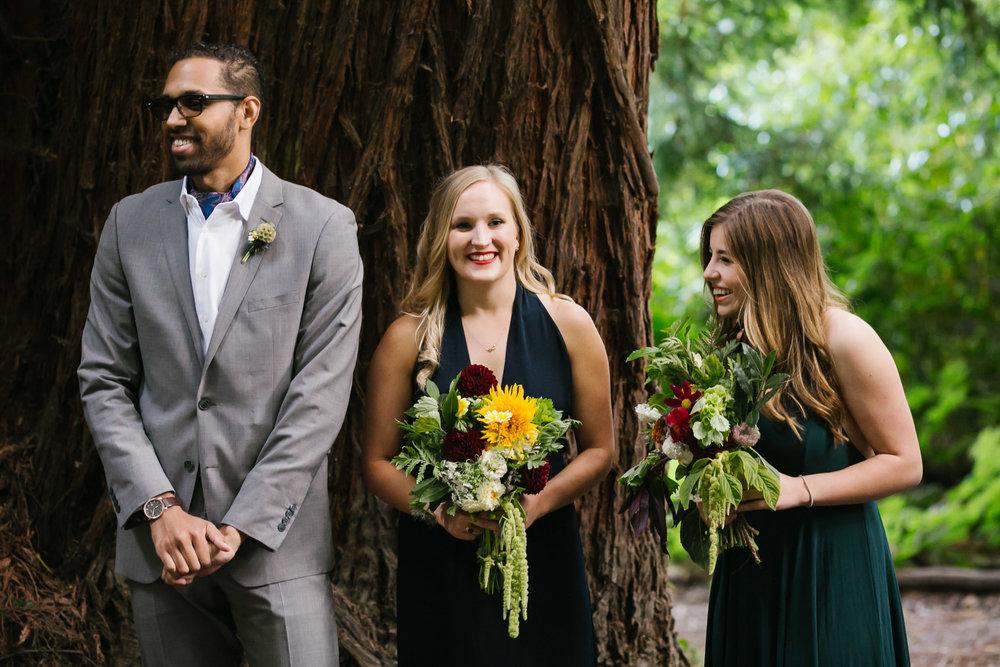 Bridesmaids laugh during wedding ceremony under the redwoods