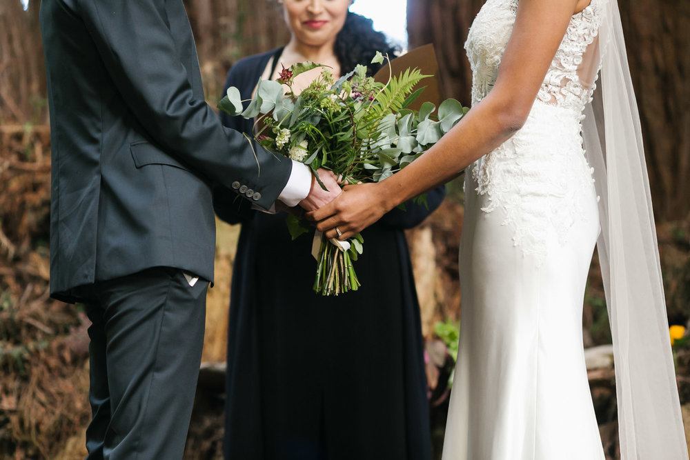 Wedding couple holding bouquet together during ceremony under the trees