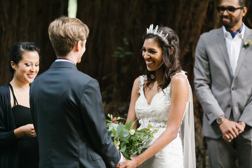 Bride wearing crystal crown and veil cape smiles at her groom during ceremony