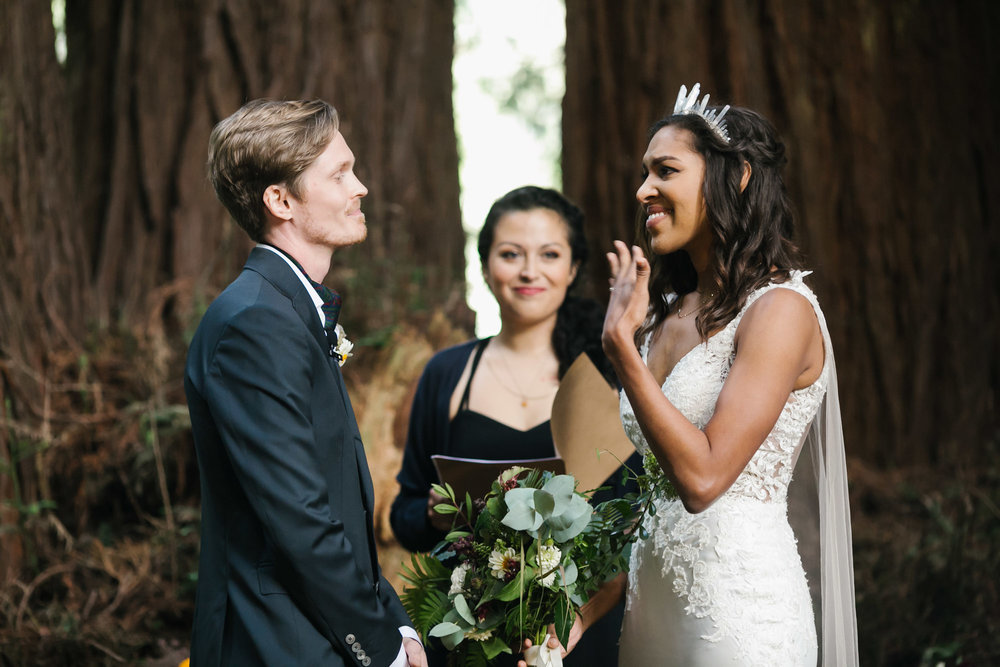 Bride gets emotional during ceremony in redwood grove