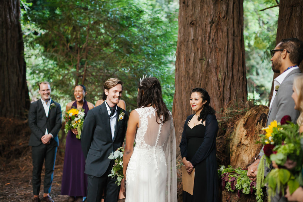 Groom smiles at his bride during ceremony in redwood grove