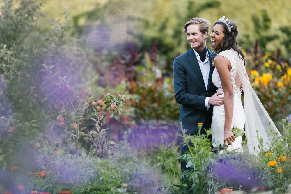 Wedding couple with flowers and apple trees at coastal farm