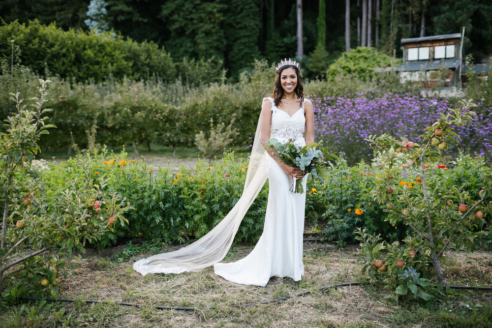 Bride in crystal crown and cape veil stands in flower field and orchard