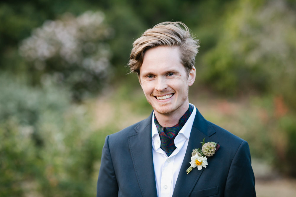 Swedish groom with blue suit and paisley ascot smiles on his wedding day