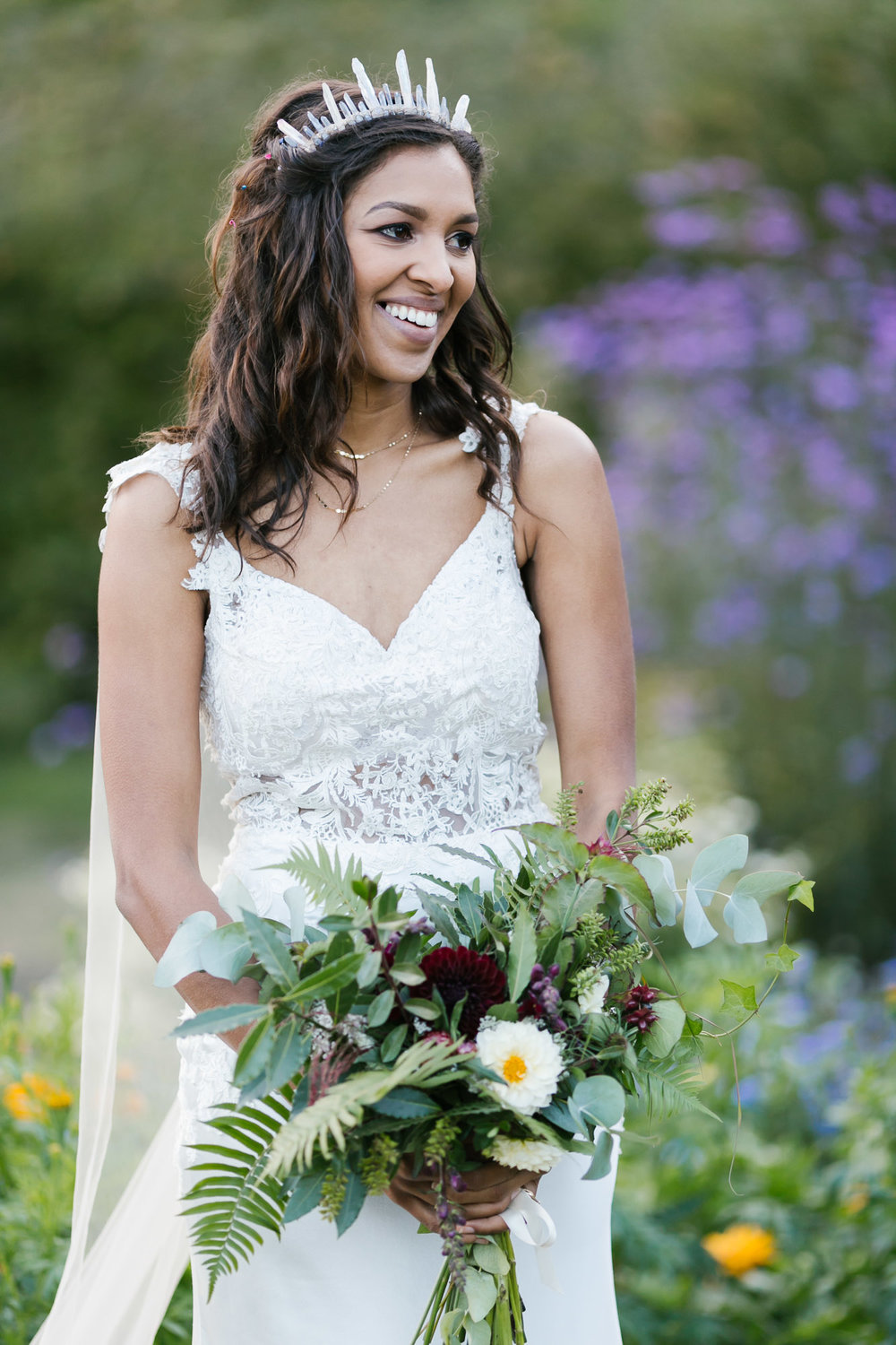 Bride in crystal crown and custom lace dress smiles on her wedding day
