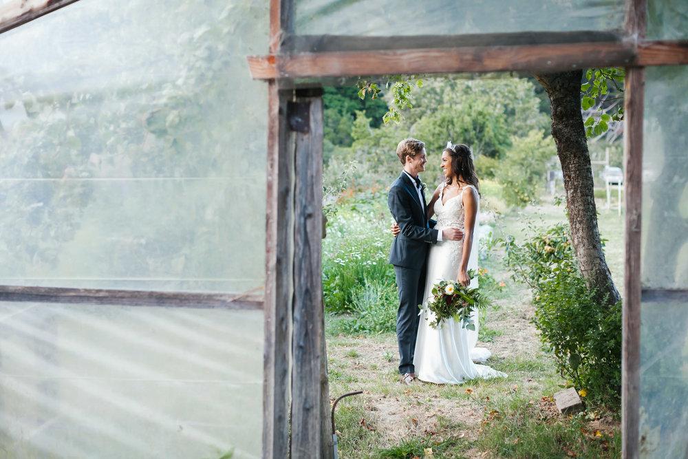 Wedding couple smile on coastal flower farm with greenhouse