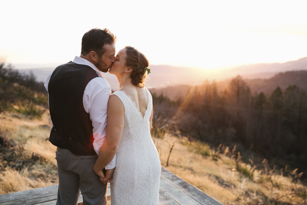 Wedding couple kiss at sunset amidst wildfire damage