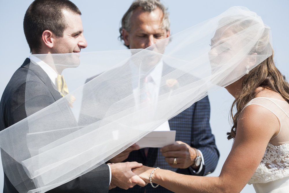 Bride laughs as the wind sweeps her veil during her wedding ceremony