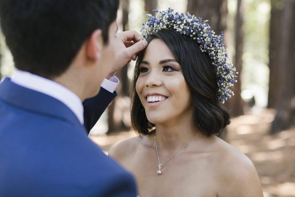 Groom fixes bride's hair and flower crown in the redwoods
