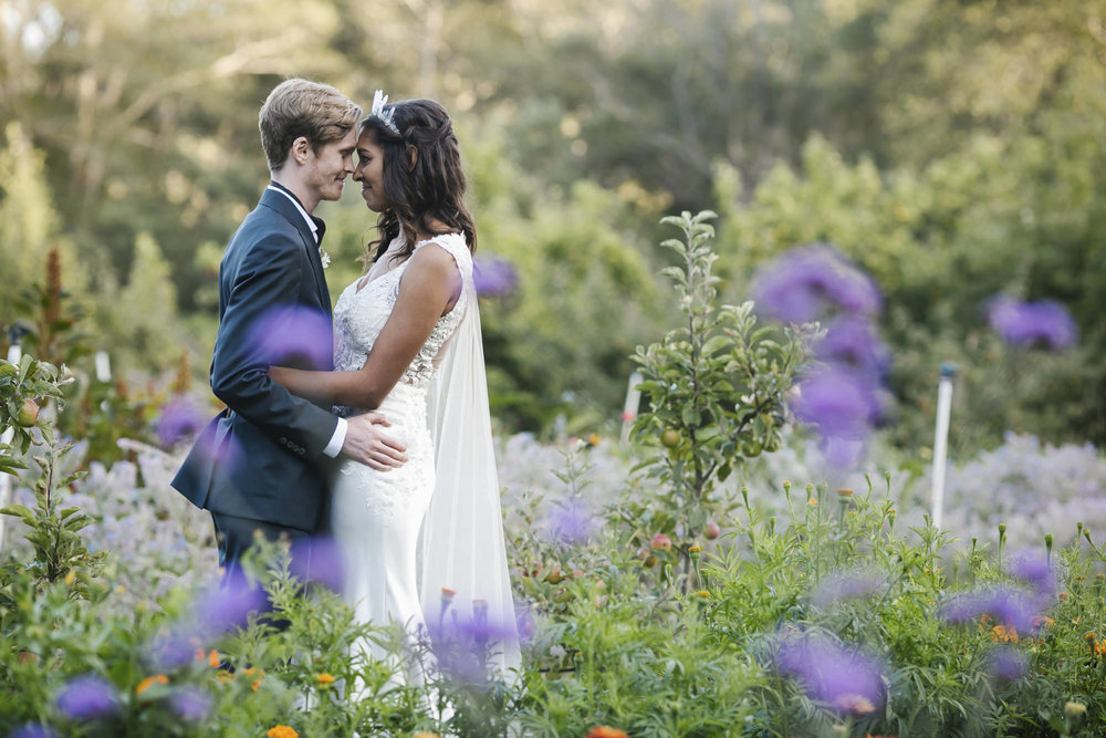 Bride and groom hold each other in a flower field on a farm