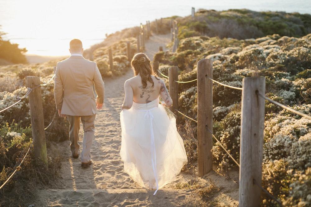 Wedding couple walk down to Baker Beach during golden hour