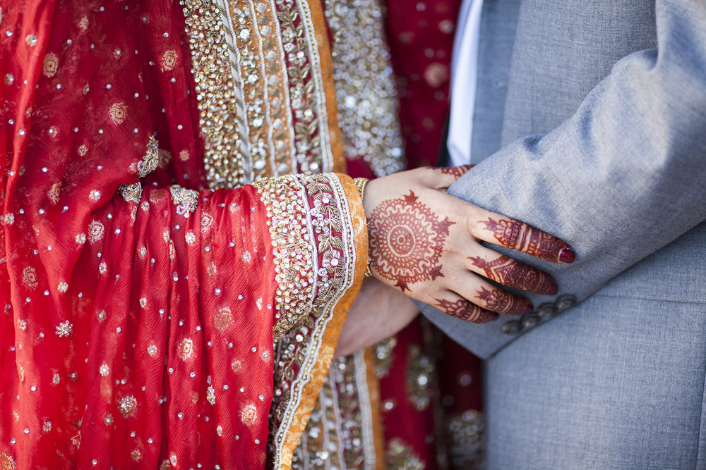 Indian bride with henna hand tattoos holds on to her groom