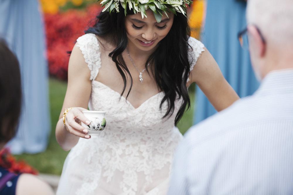 Bride with leaf crown kneels for tea ceremony