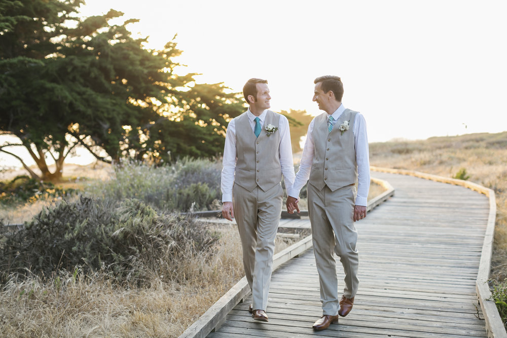 Same sex couple walk holding hands down a boardwalk in Cambria