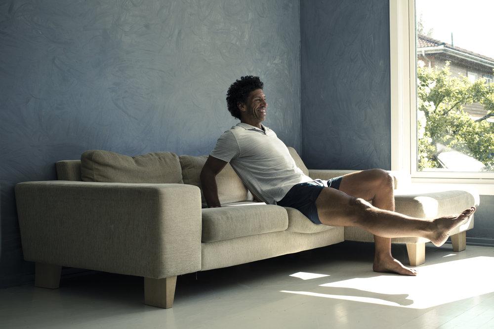 SOFA-CRUNCH: (Høres ut som en sjokolade, ikke sant? :-)  Sitt ytterst på sofaen, strekk ut det eine beinet og len overkroppen bakover. Beveg overkroppen fram og trekk kneet mot brystet. Hold i eitt sekund. Bytt bein.