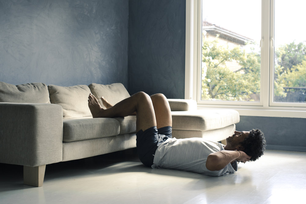 SIT-UPS: Legg føttene i sofaen og press korsryggen mot golvet. (Sjå gjerne for deg at du har eit løvblad under deg som du heile øvelsen igjennom skal presse ned mot golvet). Dra deg rolig opp mot knærne så høgt du klarar utan at korsryggen blir løfta opp frå golvet. Hold i eit sekund og gå rolig ned igjen.