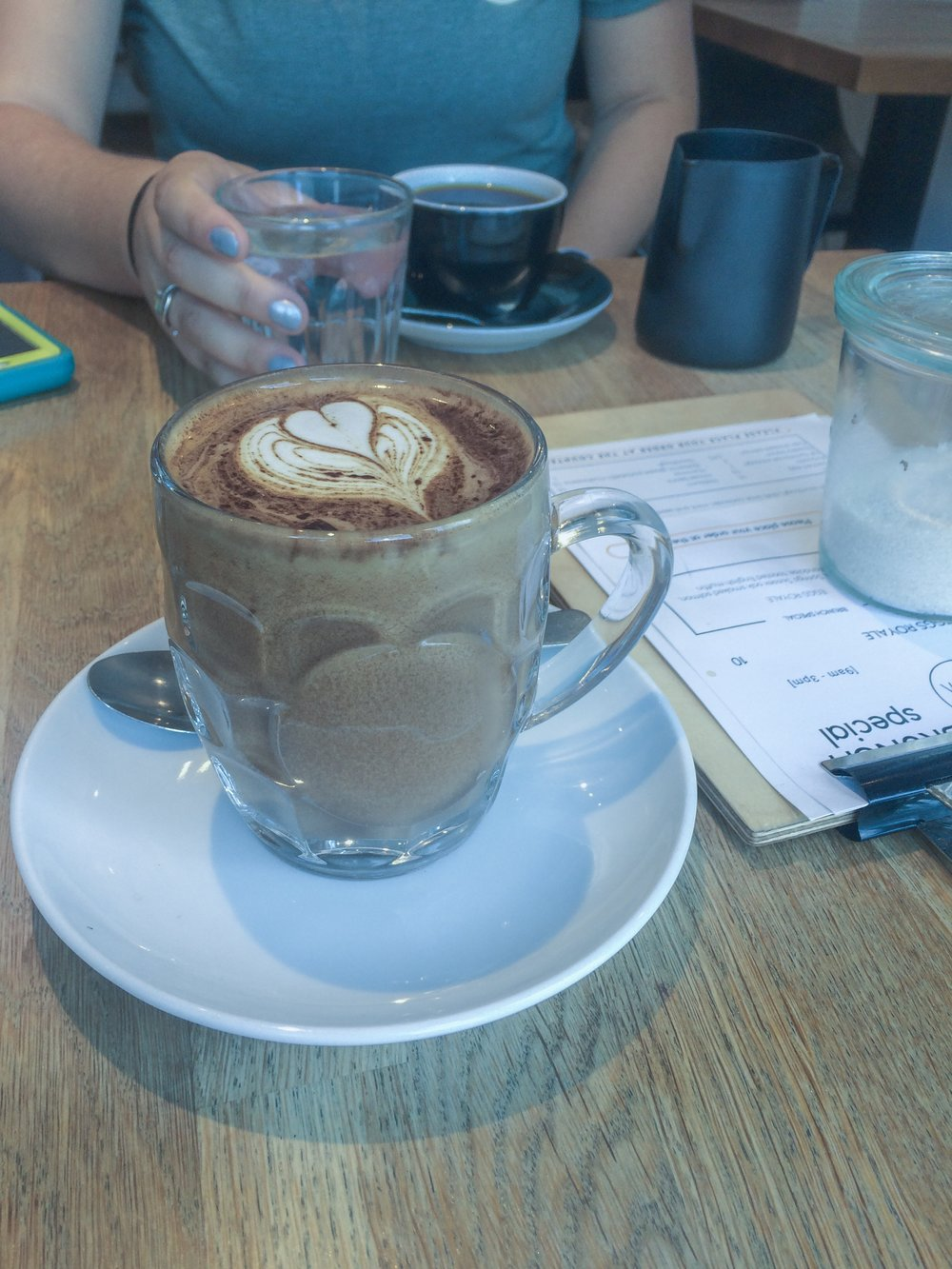 Image Description: a mocha in a glass cup with a heart design on the top sits on the table closest to the camera. Across the table, there is someone in a blue t-shirt with a cup of coffee in a black cup in front of them. Only their chest is visible. They hold a water glass in their left hand, nails painted with silver polish. A menu sits on the table next to them, with a glass jar full of sugar on top of it.