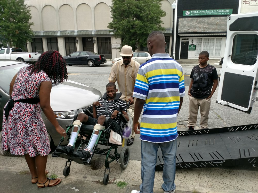 Jaekwon Williams is being transferred to a van with assistance from his mother, Jasmine Williams, and her fiance, Dwight Macklin, as sons Melvin Williams, far right, and LaDarian Williams look on Tuesday. Williams suffered permanent brain damage from nearly drowning at the Lions Adventure Water Park four years ago. Photo: Junious Smith