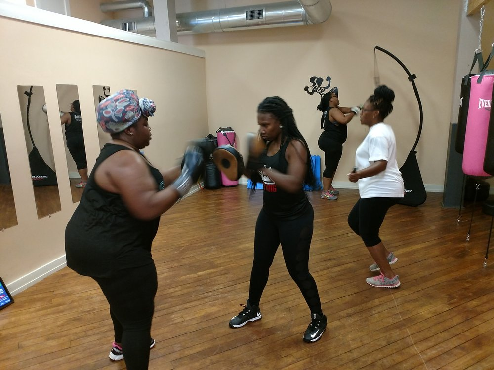Latesha Strickland, center, trains Janiel Brown during a workout Tuesday at PittFit SheBox gym while Janessa Gardner (white shirt) and Jahnesee Farris do individual exercises. Photo by Junious Smith III / Neuse News