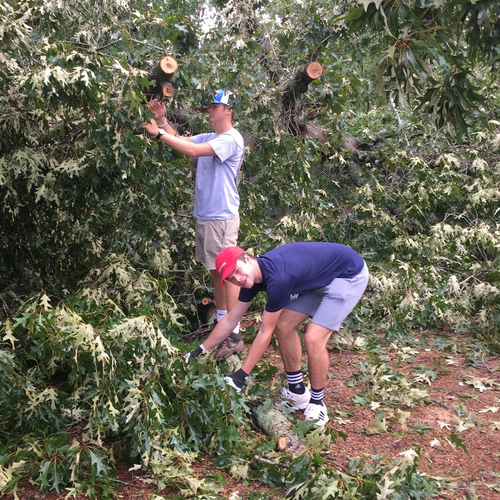 APA students Brandon Zoltek and Thomas Paris help clear storm debris at Northwest School.