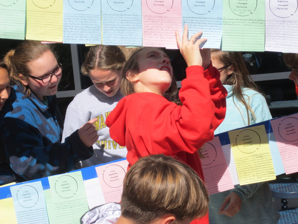 "(left to right) Nell Mason Morris, Mary Neal Cheek and Bailey Franklin, surrounded by middle school friends, enjoy reading student responses to ""A Day Writing Changed the World."""