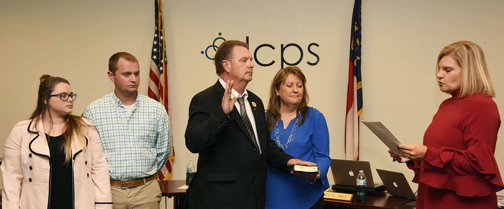 The Lenoir County Board of Education followed the swearing-in of three members — including Billy Davis, above middle — who were reelected in November by voting Monday night to keep its leadership in place. Photo by Junious Smith III / Neuse News