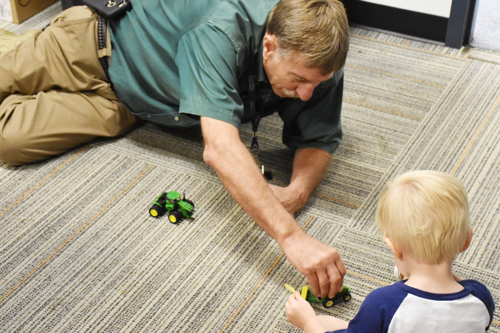 Roger Dail plays with toy tractors with Lenoir County Emergency Planner Samuel Kornegay's 2-year-old son, Andrew, on Sept. 22, at the LCES headquarters. Dail has stressed with his employees the importance of family. Photo by Bryan Hanks / Neuse News