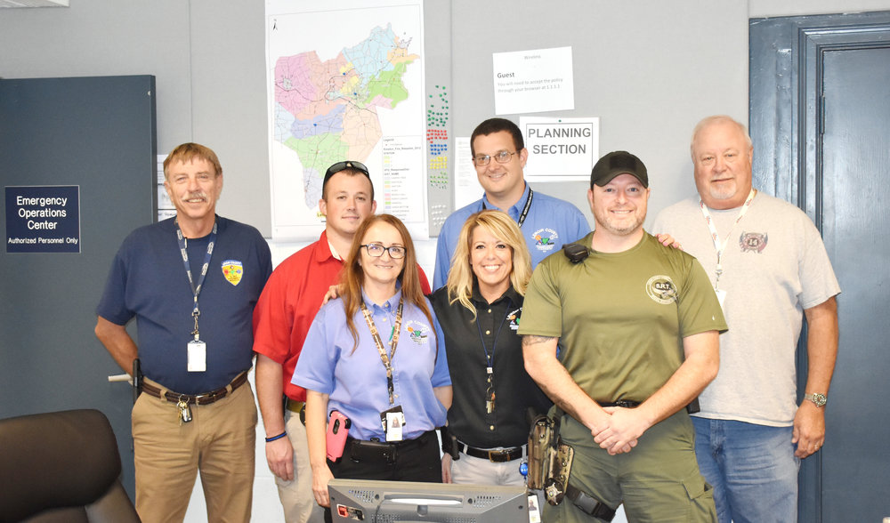 Some members of the Lenoir County Emergency Operations Center pose for a photo on the final day of the EOC's operation following Hurricane Florence on Sept. 24. They were, front row, from left, LCES Assistant Director Jerri King, 911 Operations Manager Paige Johnson, Lenoir County Sheriff's Office Sgt. Chris Jenkins; back row, LCES Director Roger Dail, Lenoir County Fire Marshal Dustin Burkett, Lenoir County Emergency Planner Samuel Kornegay and Food Unit Leader Butch Mull. Photo by Bryan Hanks / Neuse News