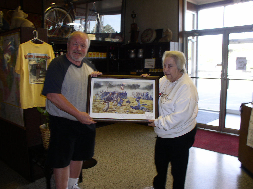 Raymond Reed and Jane Phillips at King's Restaurant holding a picture of the Stephen McCall's painting of the Lass mass capture of the Civil War.