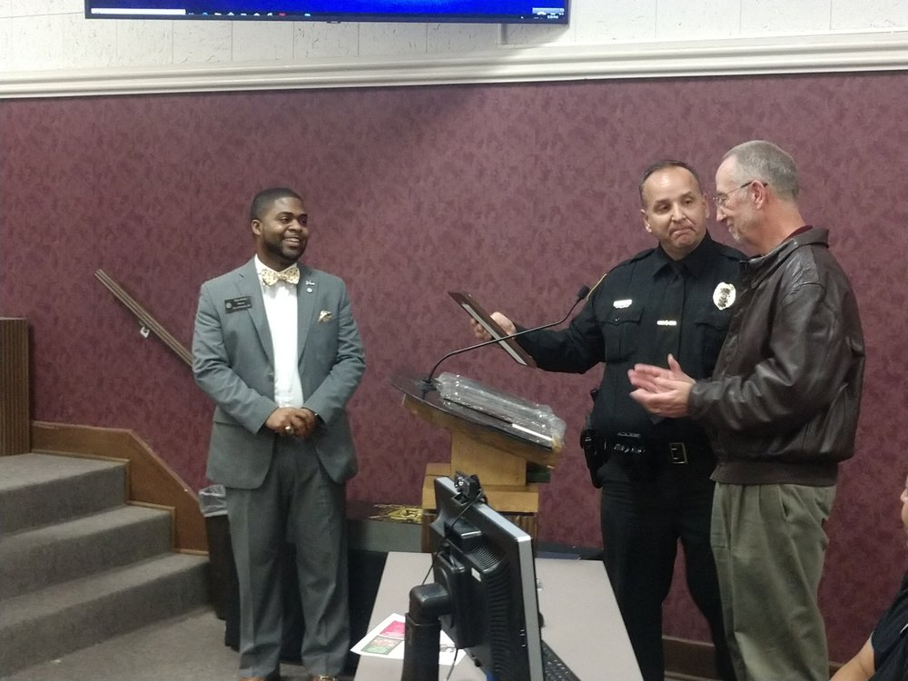 Retired Kinston Police Department Public Information Officer Woody Spencer, right, prepares to receive his plaque from KPD Major Tim Dilday as Kinston Mayor Don Hardy looks on during Monday's City Council meeting. Photo by Junious Smith III / Neuse News