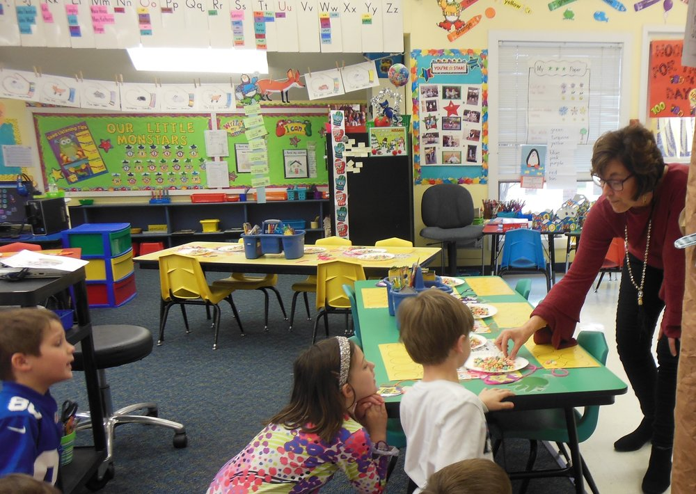 Teacher Eva King explains to her kindergarten class how to make Fruit Loop necklaces. Submitted photo