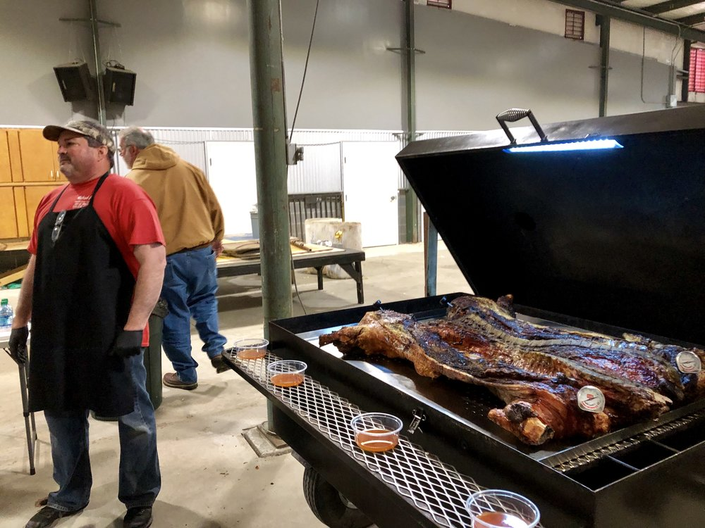 Billy Narron of Middlesex stands beside his cooked pig at the BBQ Summit. Photo by Catherine Hardee / Neuse News