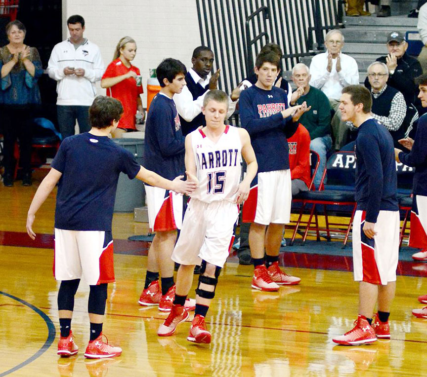 Tyson Creech, in a knee brace following ACL surgery less than four months earlier, runs out to a standing ovation during senior night activities in February 2015 at Arendell Parrott Academy. Although he didn't start the game, he played the final 30 seconds of the contest. Photo courtesy Hardy Creech and family