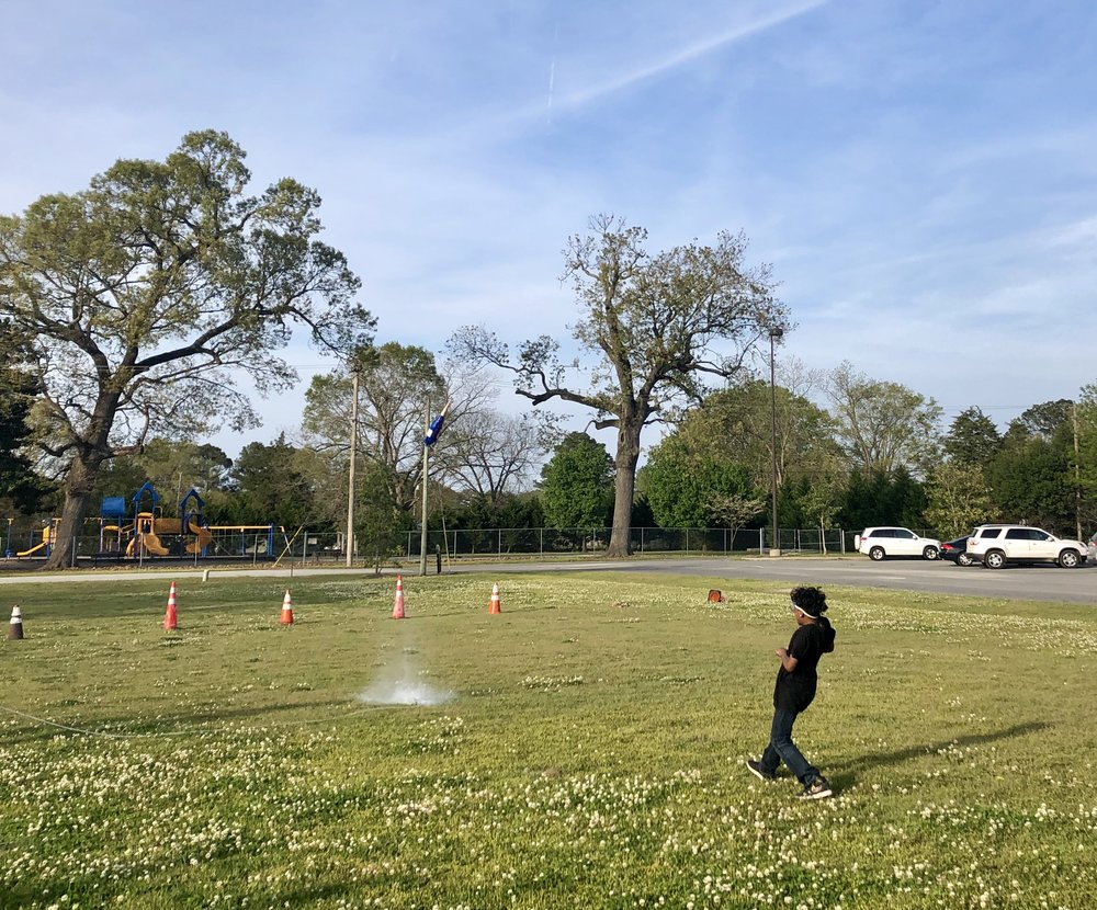 Jeremiah Waters sets off his bottle rocket. Photo by Catherine Hardee / Neuse News