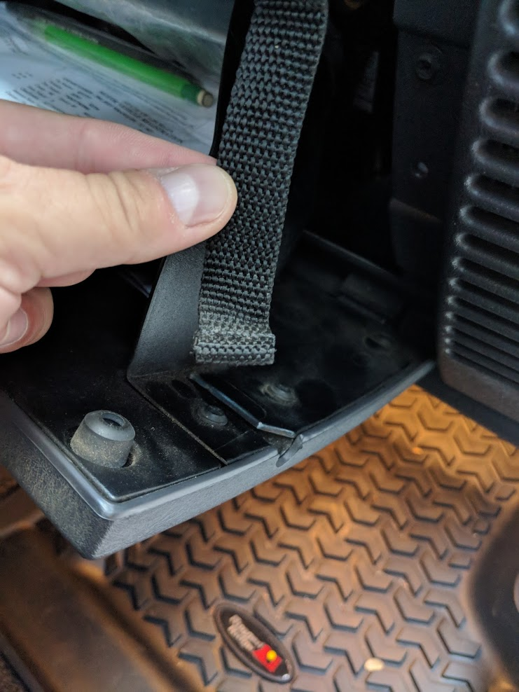 Unhook the glove box safety strap to access the fuse box on the Jeep Wrangler TJ