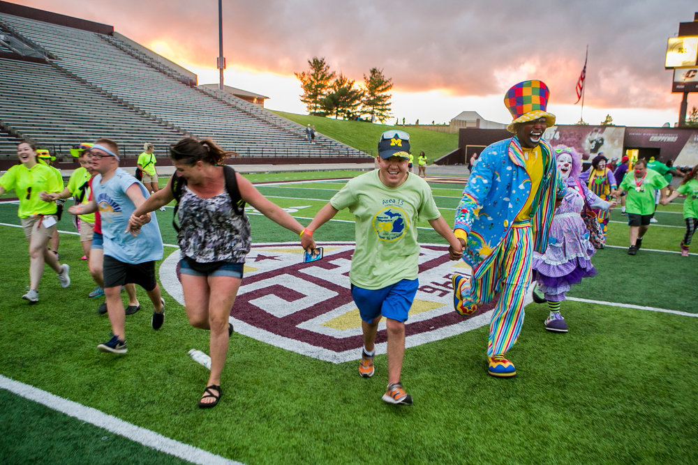 Athletes, volunteers, chaperones and the Mott Campus Clowns from Mott Community College join hands and run to the center of the football field at Kelly/Shorts Stadium after the Closing Ceremony of the 2018 Special Olympics of Michigan on Friday, May 31, 2018 in Mount Pleasant, Mich.