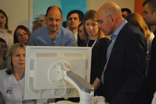 Diagnosing Ebstein anomaly: Doctors Frank Cetta (center) and Joe Dearani (right) work with the local echosonographer to diagnose a young child as physicians from all over Russia look on.