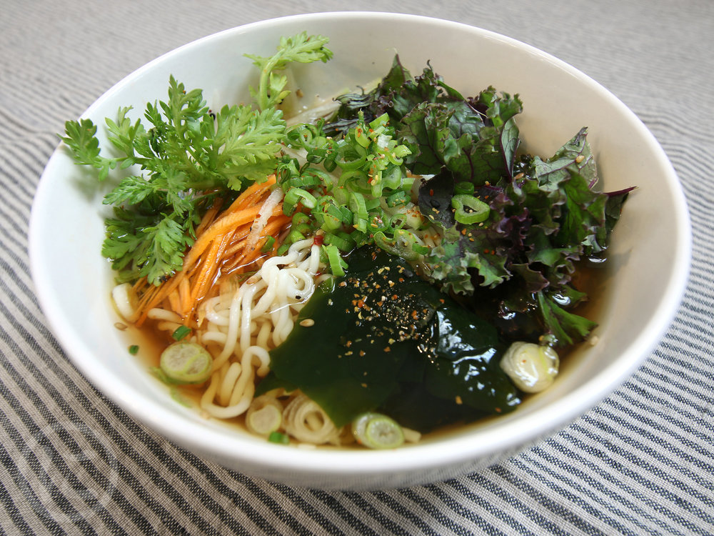 Hot Noodles in Vegan Broth  Gluten-free noodles in vegan broth with seasonal vegetables, scallions, yuzu, spices.