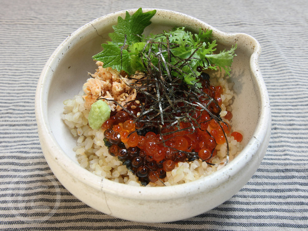Ikura Don  Salmon roe, seared salmon, baby arugula, nori seaweed, wasabi over brown sushi rice.