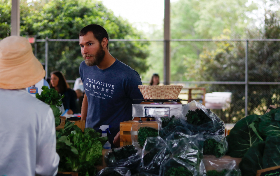 Josh Johns of Hickory Hill Farms speaks to a customer at the Athens Farmer's Market at Bishop Park in Athens, Georgia, on Saturday, April 14, 2018.