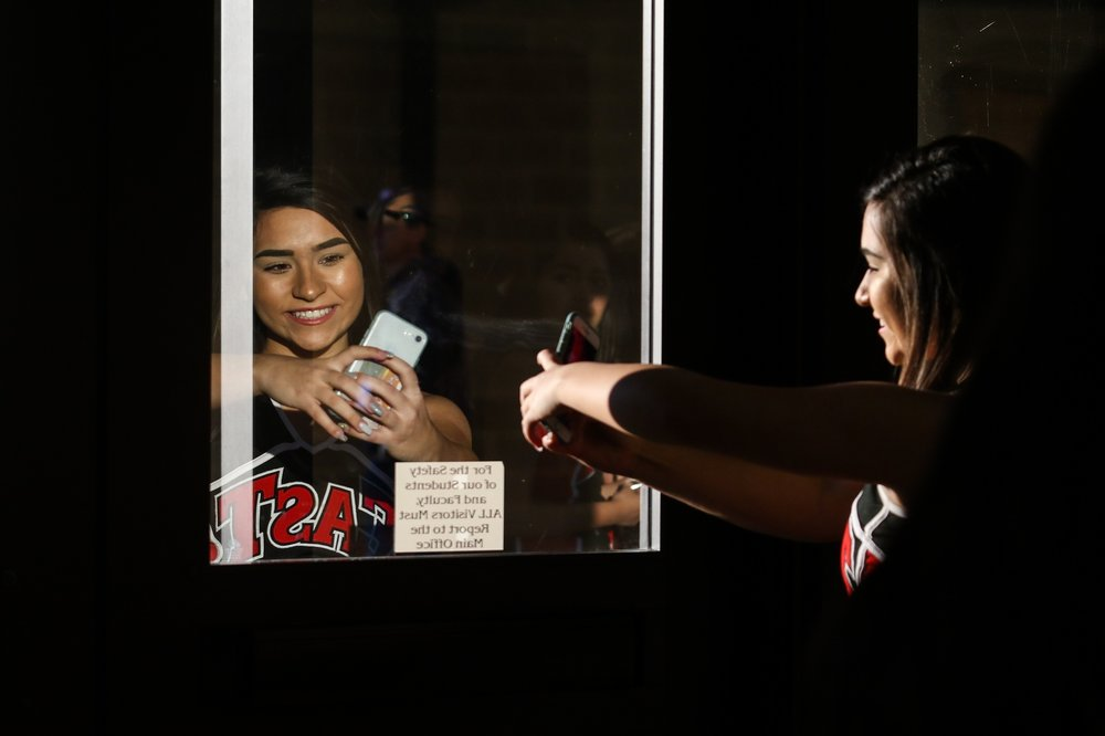 Victoria East High School cheerleader Kendall Karnowski, 17, takes a selfie outside the gymnasium at Victoria East during halftime of the boys basketball game against Victoria West on January 5, 2019.