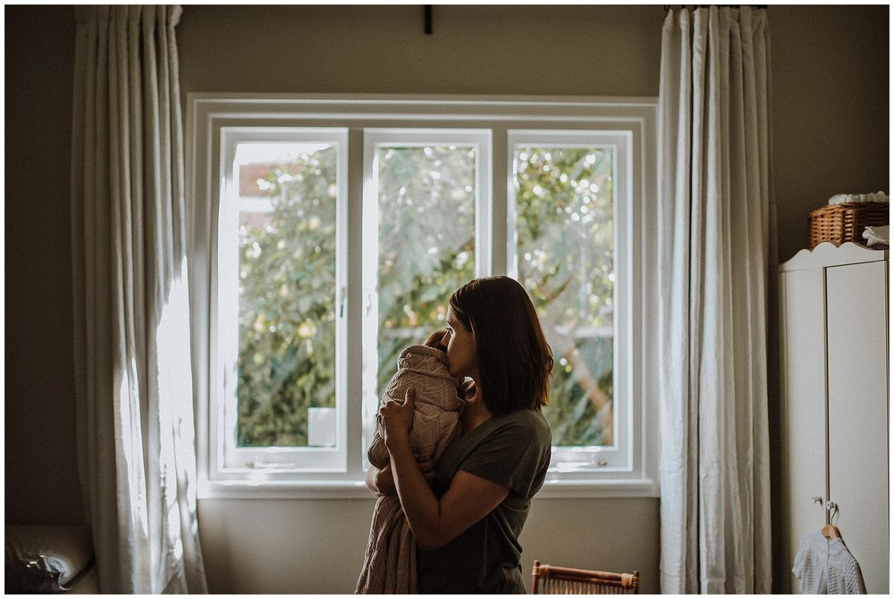 Mother holding newborn in front of window