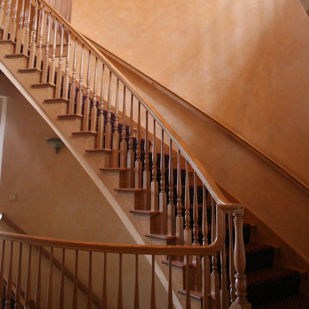 Beautiful balusters (spindles) offer support to a flowing handrail for this custom staircase.
