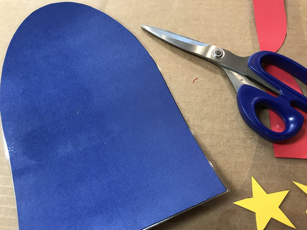 """STEP 5: Use scissors and an Exacto blade cut the pieces away from the bigger sheets of lamination film. Make sure to leave about 1/8""""-1/4"""" of laminating film around the edges because the film does not adhere to the paper, it adheres to itself."""