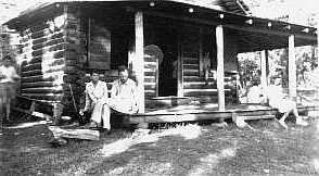 Cabin with porch. Man siting on porch is Mr. J. Brackin Kirkland.