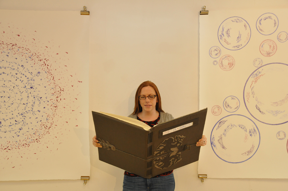Image description; me holding the giant handmade book in an art gallery, between two giant wall mounted ink patterns.