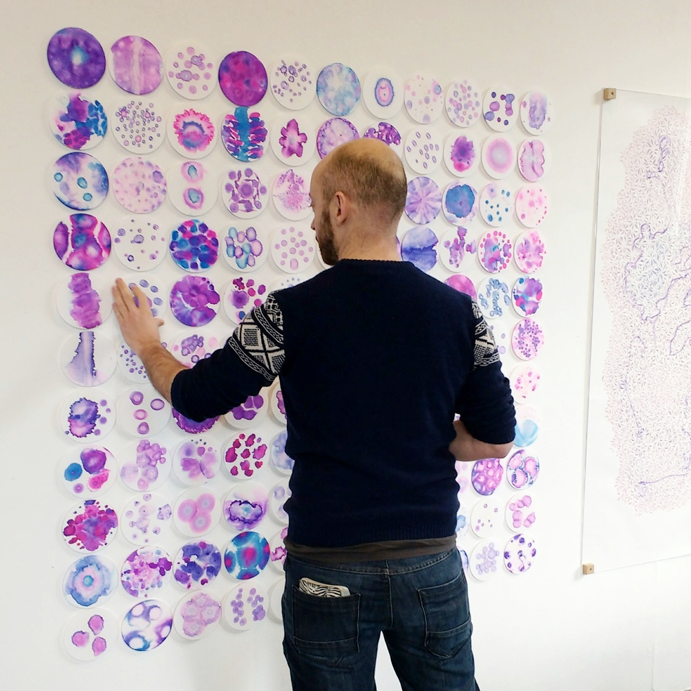 The array of ink patterns mounted on perspex with velcro, being rearranged by an exhibition visitor