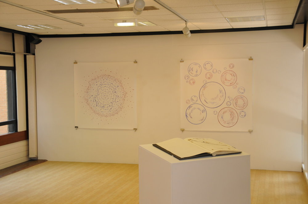 Two 1.5 m sq ink patterns hanging on a gallery wall, with a giant book on a plinth between them