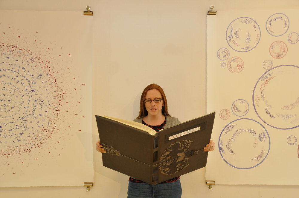 Me holding a giant book, standing between two 1.5 m sq ink patterns