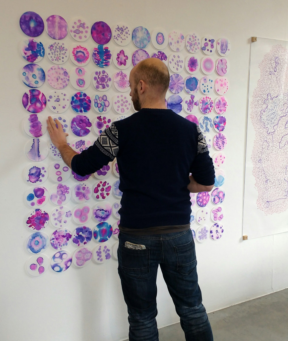 Image description; an array of 11x11 circular abstract pink and blue patterns, wall mounted, being rearranged by a gallery visitor
